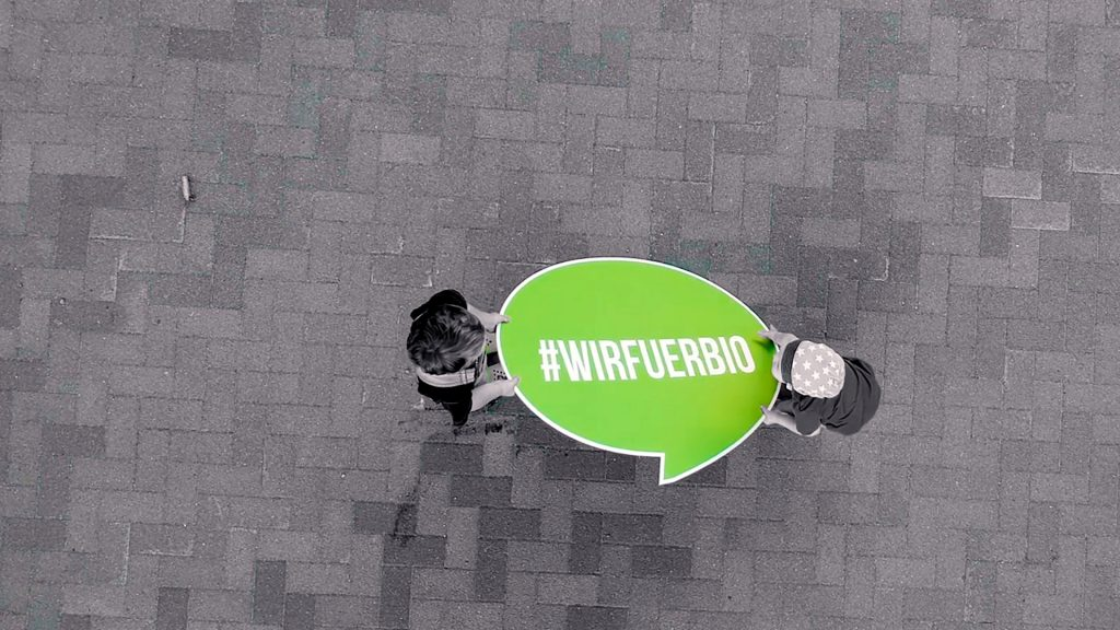 Zwei Kinder halten #wirfuerbio-Logo