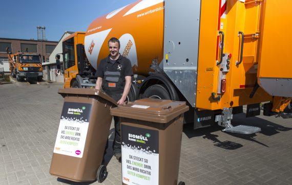 Mann vor Müllfahrzeug nimmt Biomülltonne