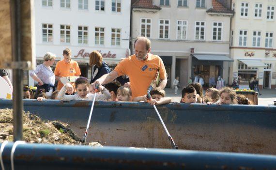 Mann und Kinder mit Abfall-Greifzangen