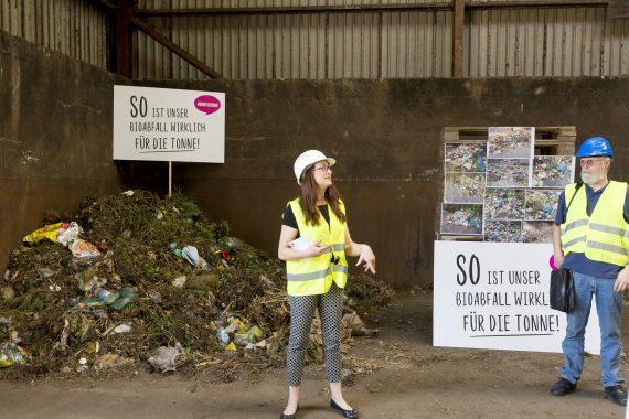 Personen vor Plakaten und Abfallhaufen