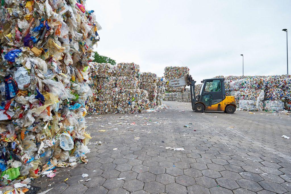 Gestapelte Müllballen und Radlader