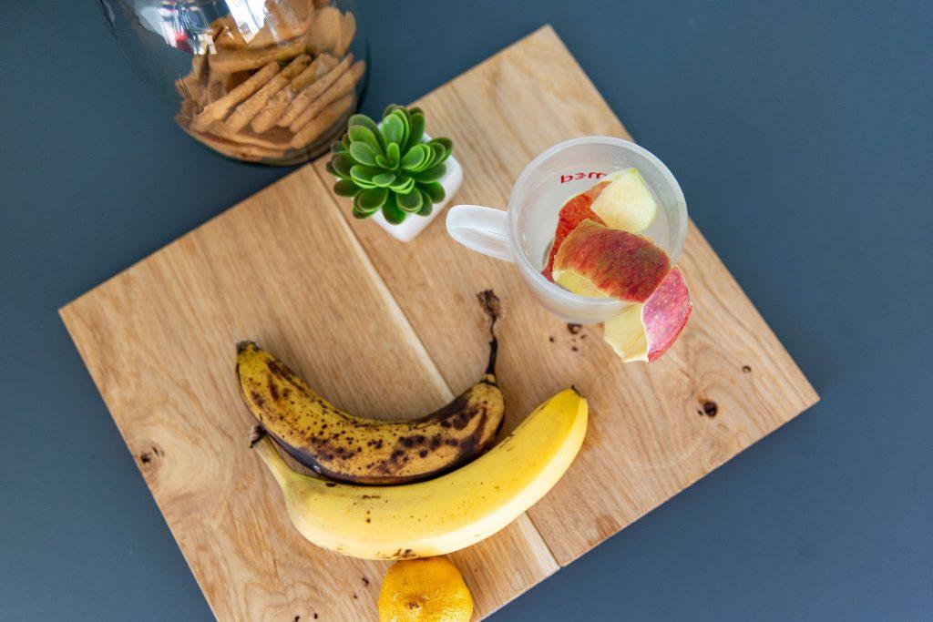 Holzbrett mit Obst und Obstschale