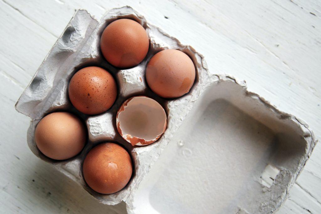 Eierschale und ganze Eier in Karton