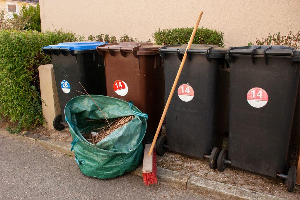 Gartenabfall-Sack vor aufgereihten Abfallbehältern