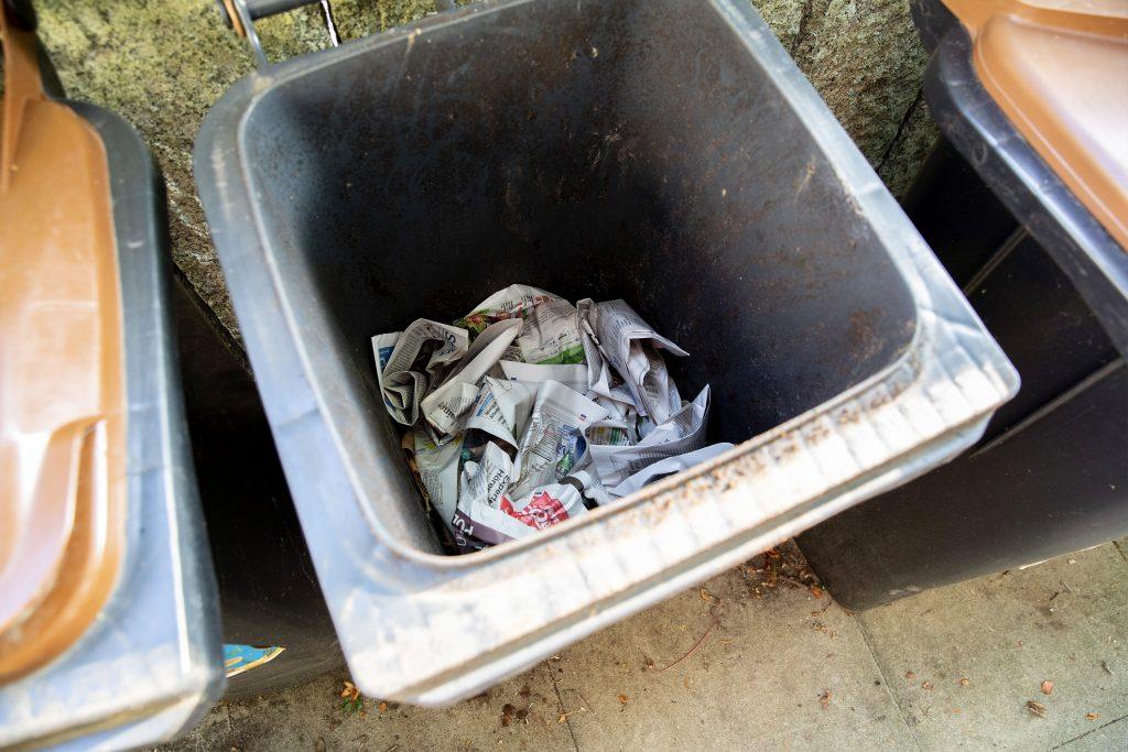 Zerknülltes Zeitungspapier in geöffnetem Abfallbehälter