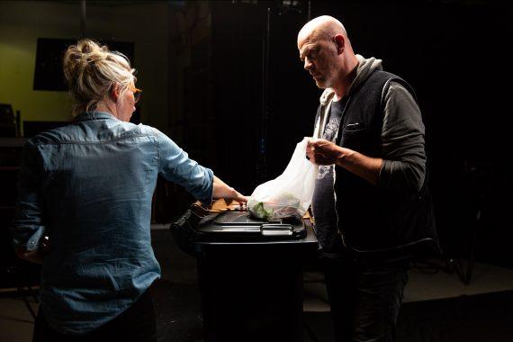 Frau zeigt Mann etwas an Abfallbehälter