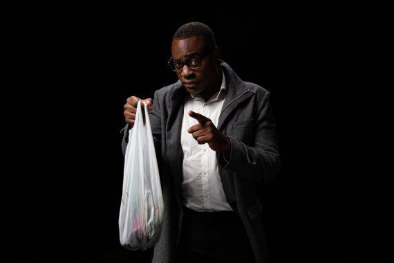 Mann hält Plastiktüte und erhebt Zeigefinger