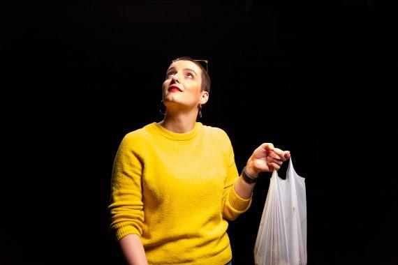 Frau mit Plastiktüte schaut hoch