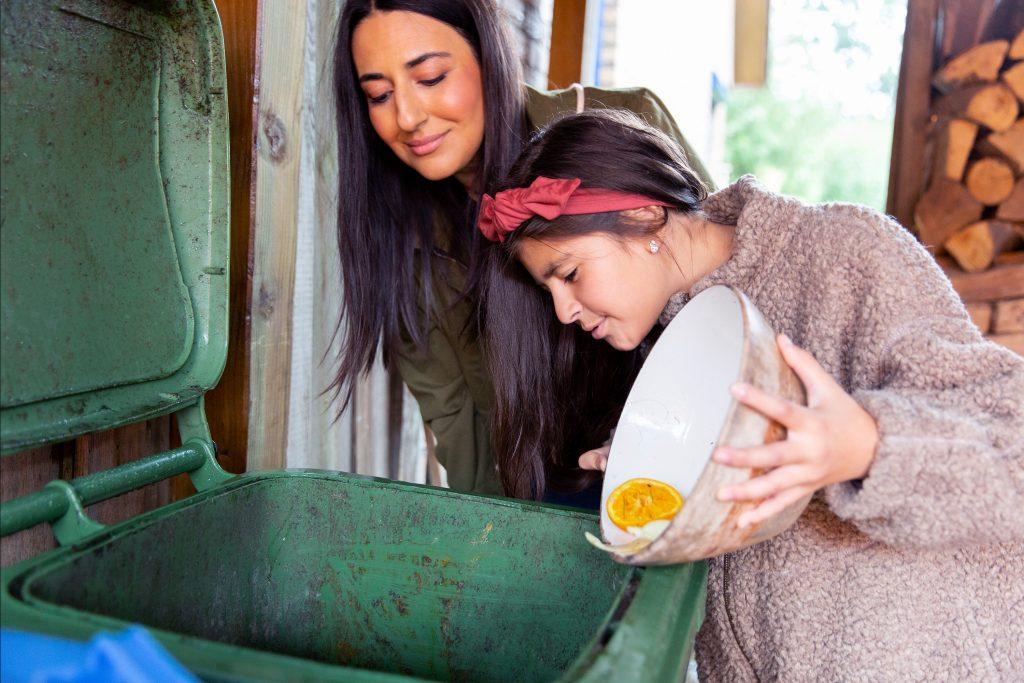 Frau und Mädchen geben Bioabfälle in Behälter