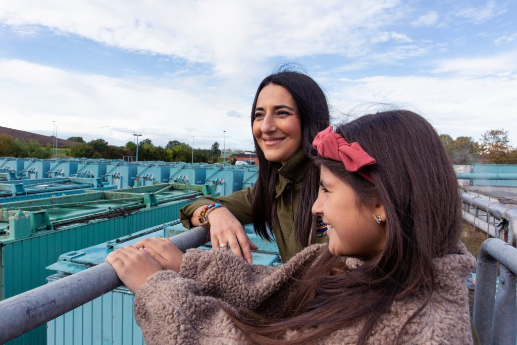 Frau und Mädchen schauen auf Bioabfallbehandlungsanlage
