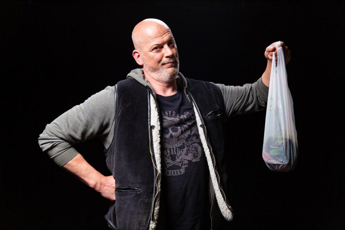 Mann mit Plastiktüte stützt Hand in Hüfte