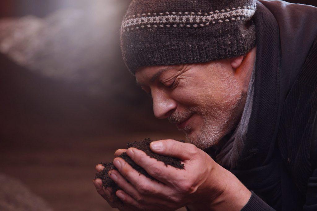 Mann riecht an Kompost