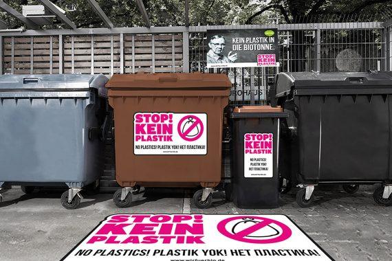Abfallbehälter mit Tonnenaufklebern hinter Bodenaufklebern