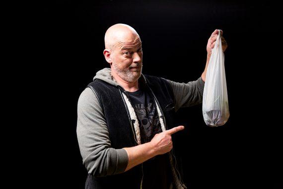 Mann zeigt auf gefüllte Plastiktüte