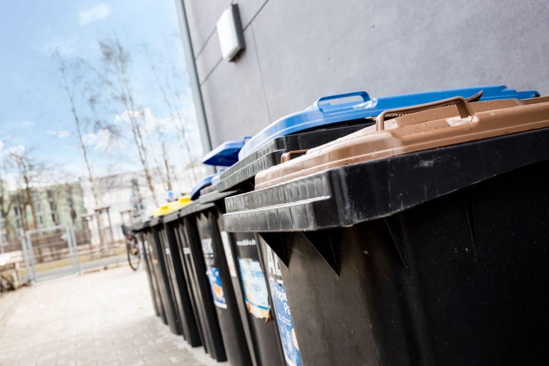 Aufgereihte Mülltonnen an Hauswand